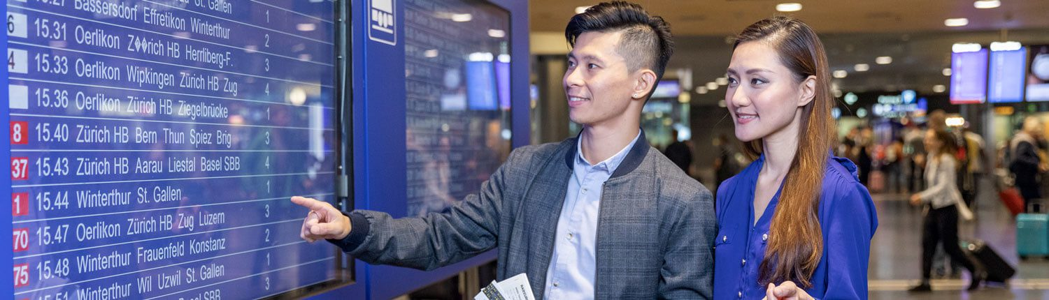 Chinese Travellers in front of an electronic timetable at Zurich Airport