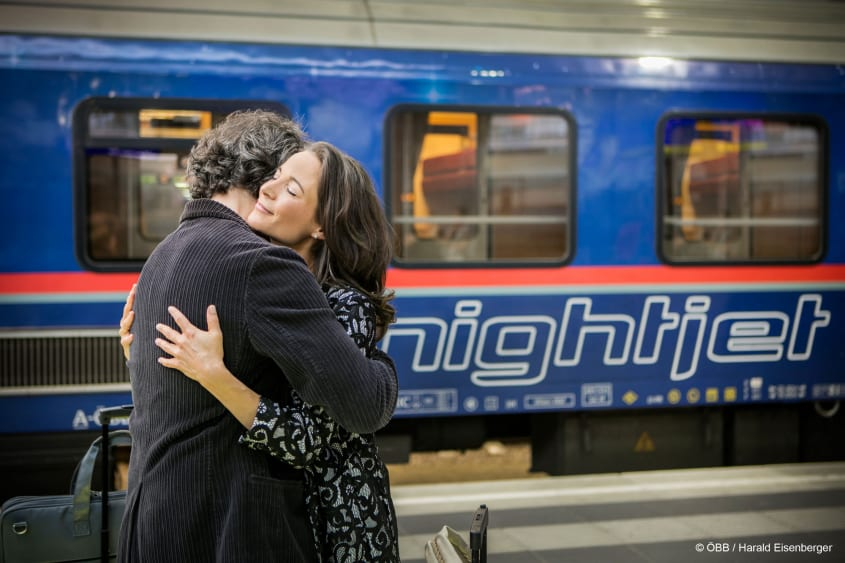 Couple hug with nightjet in the background (© ÖBB / Harald Eisenberger)